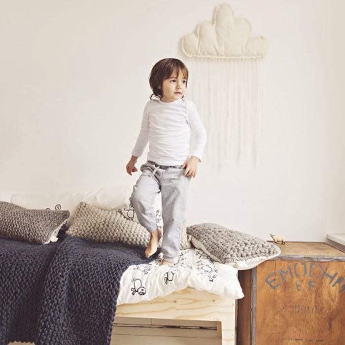 Mały chłopiec skacze po łózko z kocem wełnianym