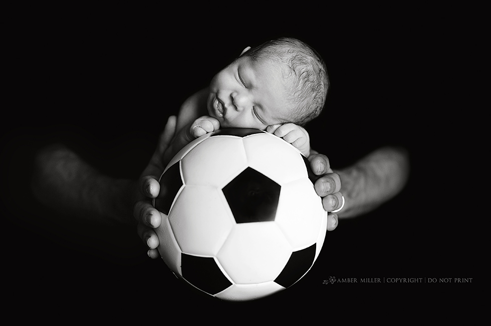 sleeping newborn on soccer ball