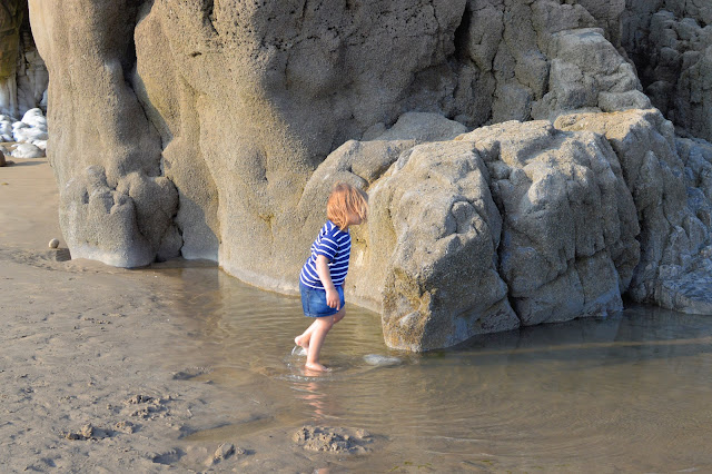 Girl paddling rock pool Pendine Sands