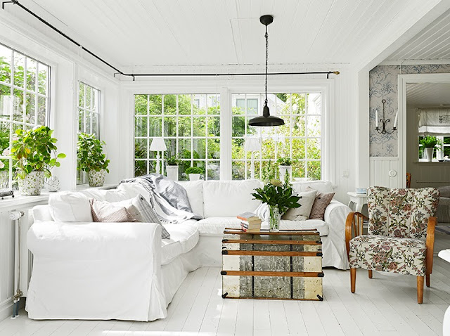 white living room Swedish cottage painted hardwood floor white slipcovered sofa