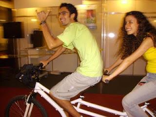 No meio dos estandes da Reatech, Diego Bruno e Sara Bentes se divertem em uma bicicleta branca de dois lugares