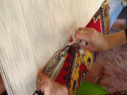 A young lady working on a rug.