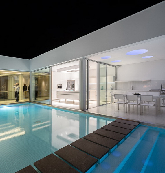 Bridge over the swimming pool in Modern Villa Escarpa by Mario Martins at night