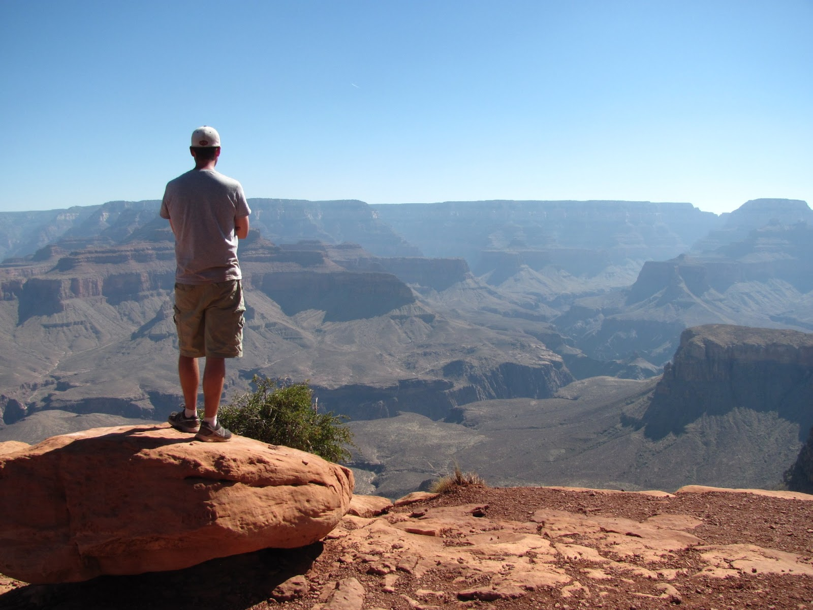 Cory stands on a rock on the edge of the canyon  in the morning at Grand Canyon National Park, Arizona