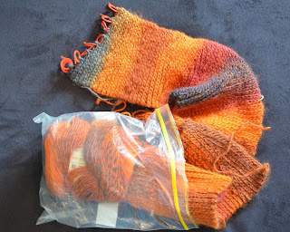A scarf in progress half in and half out of a clear snap lock bag. Made of slip stitch crochet, the scarf's colours graduate from a dark charcoal through reds, oranges and gold.