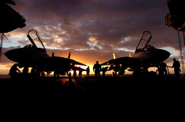 "The sun sets behind a pair of F-14D Tomcats assigned to the ""Tomcatters"" of Fighter Squadron Three One (VF-31)"