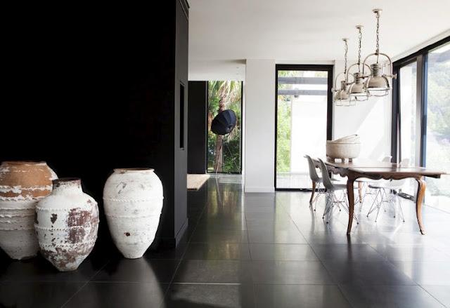 comedor de estilo moderno y minimalista con lamparas industriales mesa de madera y sillas de los Eames con dos paredes negras