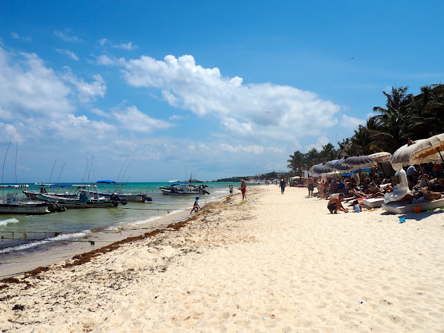 White sand & boats in the ocean at the beach in Playa del Carmen, Mexico