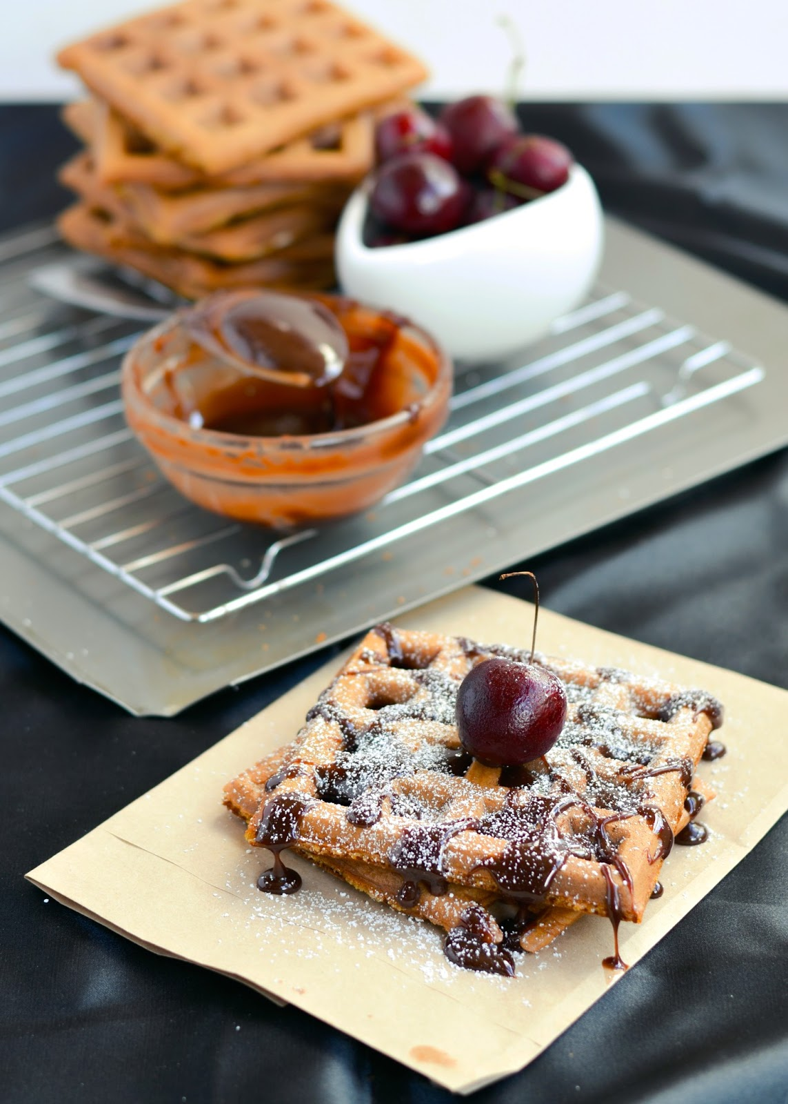Coconut sourdough waffles with dark chocolate sauce and fresh cherries