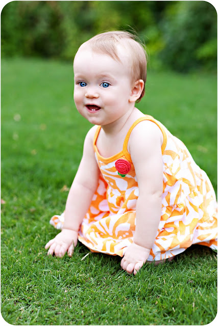 Toddler tries to stand in grass wearing a bright sundress at the end of a family photo session