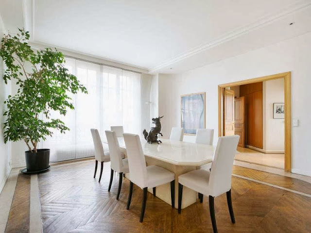 Dining room in a Paris apartment with herringbone wood floor, large windows, white high back chairs and a long hexagon table