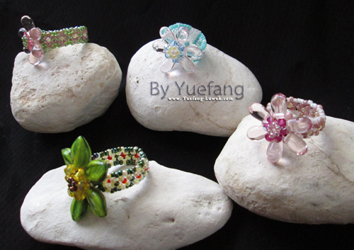 four_beaded_flower_rings_displayed_on_white_stone_and_black_background