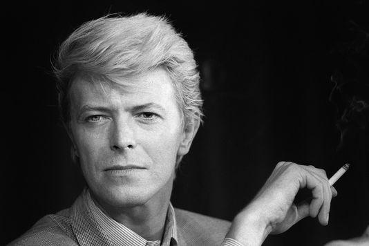 image en noir et blanc de David Bowie, cet artiste est décédé d'un cancer le 10 janvier 2016. la photo le montre fumant une cigarette et fixant l'objectif