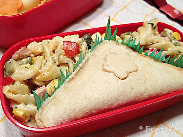 Zwei Toastecken mit Pinienkern-Rucola-Aufstrich und Paprika-Hirtenkäse-Aufstrich sowie Nudelsalat - Food Art
