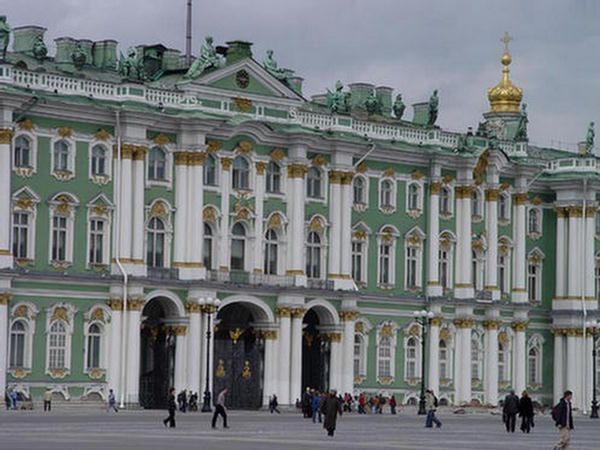 visitors in front of green and gold winter palace or hermitage museum in st.petersburg russia