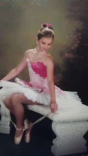 the young dancer in pointe attire sitting on a bench tying her pointe shoe
