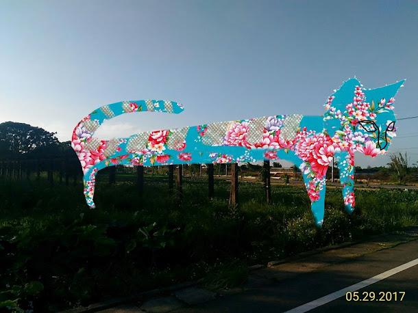 「2017桃園地景藝術節」裝置藝術《花貓愛魚》,設置於桃園觀音主展區的廣福社區活動中心旁之生態池,30米長的花貓正趴在棚架上,凝望著生態池裡的花步魚,