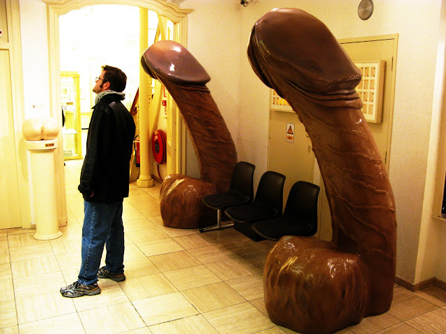 A guy at the sex museum in Amsterdam standing in front of two giant penis chairs.