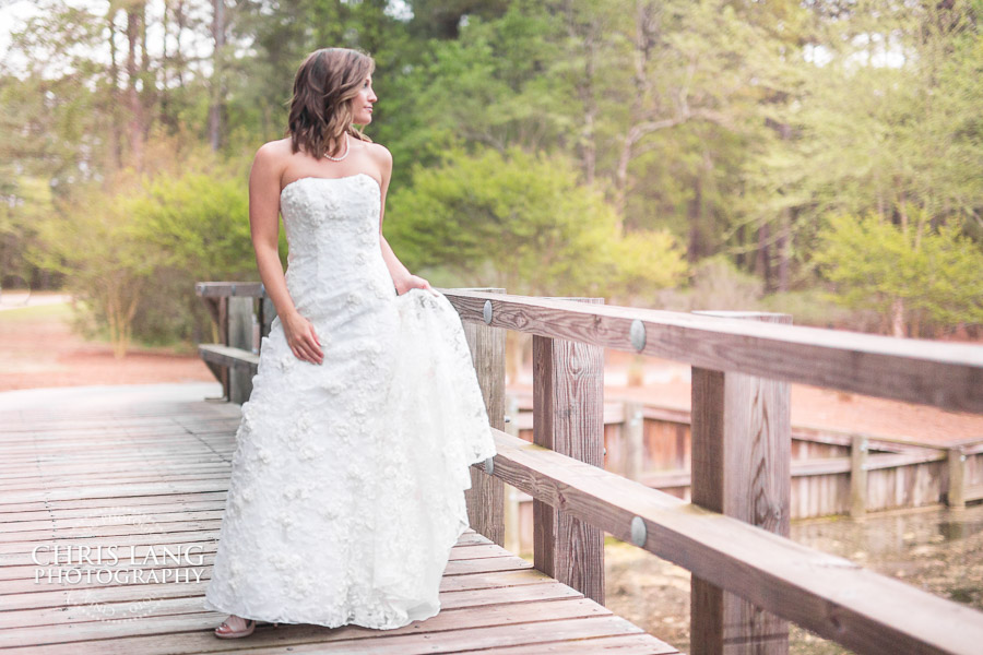 Bride in wedding dress at River Landing on the covered bridge - Rustic Bridal Portraits