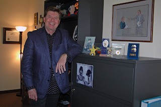 Dr. Jim Dozier in his office among mementos of his past careers.