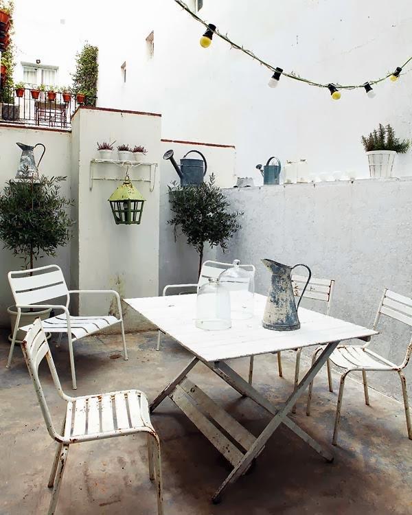 muebles de terraza de hierro con objetos antiguos de zinc