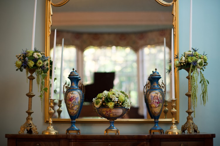 mantel with wedding flowers styled in antique vases in front of mirror