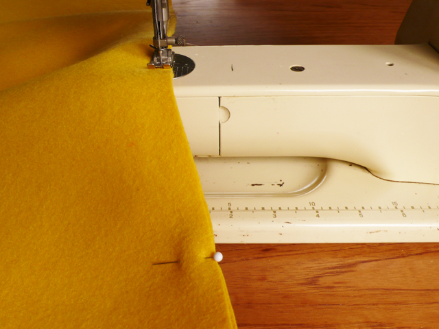 A close up of a sewing machine and pinned yellow felt fabric.
