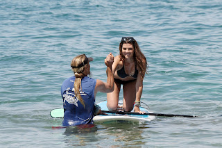 Ali Landry on her knees on a paddle board