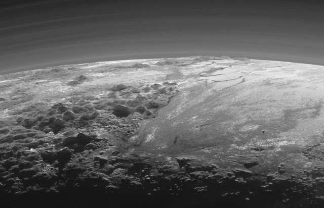 Just 15 minutes after its closest approach to Pluto on July 14, 2015, NASA's New Horizons spacecraft looked back toward the sun and captured a near-sunset view of the rugged, icy mountains and flat ice plains extending to Pluto's horizon. The smooth expanse of the informally named Sputnik Planum (right) is flanked to the west (left) by rugged mountains up to 11,000 feet (3,500 meters) high, including the informally named Norgay Montes in the foreground and Hillary Montes on the skyline. The backlighting highlights more than a dozen layers of haze in Pluto's tenuous but distended atmosphere. The image was taken from a distance of 11,000 miles (18,000 kilometers) to Pluto; the scene is 230 miles (380 kilometers) across.   Credit: NASA/Johns Hopkins University Applied Physics Laboratory/Southwest Research Institute