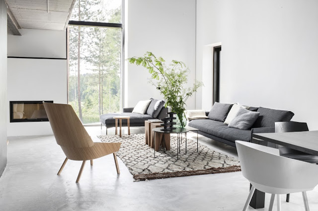 Modern neutral living room grey sofa wood chair white walls large window