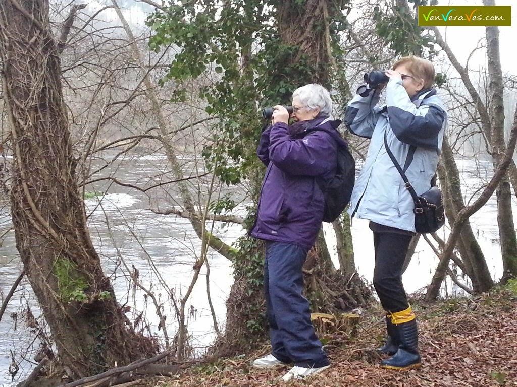 Dos mujeres observando aves con prismáticos en la orilla del río Miño