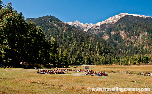 A wonderful place for adventurous campers: Sarahan, Kullu : Vandana Bhagra, Shimla : Hidden among the snow covered hills of Shrikhand Mountian Ranges, which are known for their mythological significance and is said to be one of the adobe of Lord Shiva, this unknown village beckon those with an adventurous spirit as its beautiful landscape and lush green valley will take your breath away. Many of you may get confused with Sarahan in Shimla district with its beautiful Bhimakali Temple but those you know and have been to Kullu will know this Sarahan better at 3200 metres height, and that too if they have had the zeal to walk all the way to picture its magnificent beauty.If you start your journey from Shimla then head towards Narkanda about 63 kms and then towards Nirmand which is another 28 kms approximately, with panoramic views of the Satluj Valley. From there you reach Bhagi Pul and then an uphill narrow road covering a distance of about 12 kms leads to this small village nestled among the mountains in all is pristine. Those who wish to travel by bus should be prepared for a long journey as it is nearly 176 kms from Shimla and can take up to 10 hours to reach, but of course with few stops and immense beauty to admire. Those planning to come from Beas side should be aware that there is no motorable road and would have to cross on foot from the Bishloi Pass.The HPPWD rest house situated outside the village offers decent accommodation which needs to be booked in advance but for the more adventurous laying out their tents (which of course you need to carry) in the open meadows can always be an option. With permission from the Government School nearby you can set your camp under the starry sky. The huge ground in the centre of the village is surrounded by fields, flora and fauna, water streams, waterfalls with amazing views of the snow covered hills nearby.  With so much natural beauty around it becomes quite hard to concentrate on anything and then there were these kids studying in their open air classrooms.Those rring to go can begin their trek from Kullu Sarahan to Bashleo Pass through the dense forests and green meadows to experience this place and its serenity. A one day trek to the nearest snow covered peak is an enjoyable experience as one would come across innumerable waterfalls, small stream and unexplainable natural beauty. The freshness and the virginity of the place suddenly hits you taking you thousands and thousands of miles away from your hustle bustle city life.  Other trekking options include heading towards the Jaon village to begin the Shrikhand trek through various hills, forests and streams. Village folk are often seen walking all the distance to Bangar and making it back by dinner time.The most typical feature about this village is its beautiful temple dedicated to sage Shring and gives a feeling of being a step closer to god and reaching for the sky. The use of vibrant colours, intricate artwork and unique architectural style will capture your imagination. The snow covered hills behind the templegives it a perfect backdrop of picture perfect beauty. The recently concluded two day Jhiru mela held during sangrand in April celebrates the beginning of the New Year which witnesses the village folk in their traditional dresses, dancing and singing to folk songs and wishing for prosperity.In case you plan a trip to Kullu and its better known destination do not forget to enquire about this small little village as it will equally charm you as would the other destinations.Photo credits: VJ Sharma