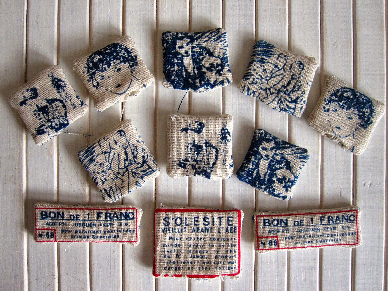 Selection of dolls house miniature cream and blue cushions with a 1920s theme. Unstuffed.