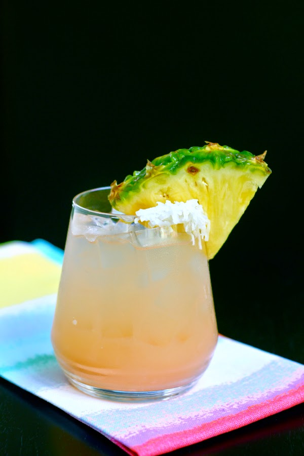 peach cocktail with pineapple coconut garnish