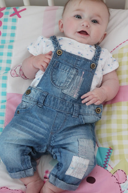 baby girl wearing denim blue dungarees with white and blue floral pattern t-shirt