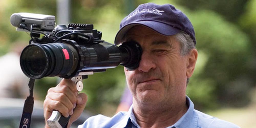 robert de niro como diretor de cinema operando lente no set do filme o bom pastor