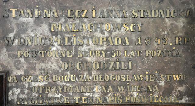 Końskie, kolegiata pod wezwaniem św. Mikołaja. Na południowej ścianie prezbiterium, pod oknem, jest tablica z napisem: STANISŁAW NAŁĘCZ I ANNA ZE STADNICKICH MAŁACHOWSCY W DNIU 24 LISTOPADA 1843 R. POWTÓRNE ŚLUBY 50 LAT POŻYCIA OBCHODZILI. NA CZEŚĆ BOGA ZA BŁOGOSŁAWIEŃSTWO OTRZYMANE I NA WIECZNA PAMIĄTKĘ TEN NAPIS POŚWIĘCAJĄ. Foto. KW.