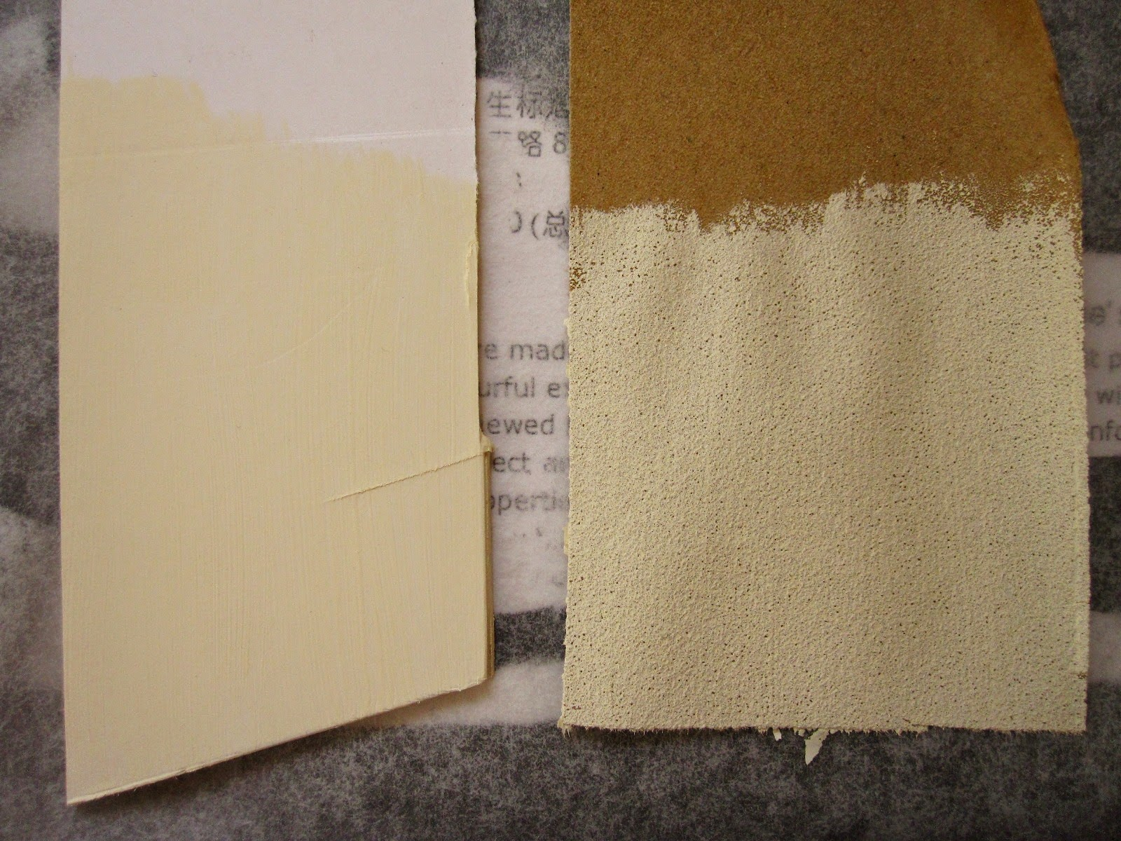 A sample iece of cardboard and a sample piece of sandpaper, both painted with cream paint, laid out to dry.