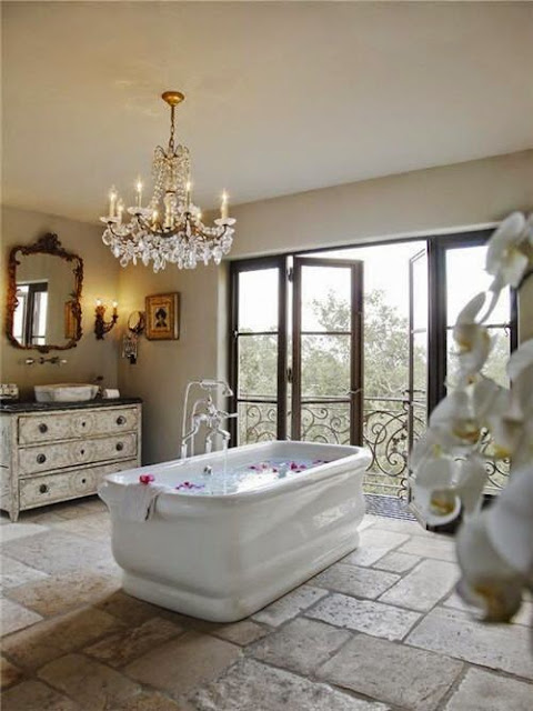 traditional rustic master bathroom stone tiles ornate crystal chandelier