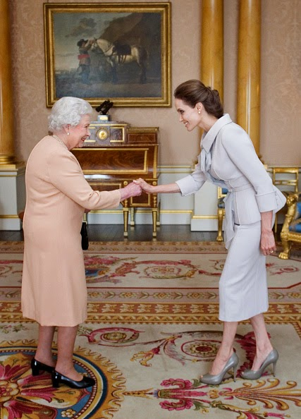 Actress Angelina Jolie is presented with the Insignia of an Honorary Dame Grand Cross of the Most Distinguished Order of St Michael and St George by Queen Elizabeth II in the 1844 Room on 10.10.2014 at Buckingham Palace