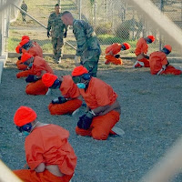 prisoners on the ground at Guantanamo Bay