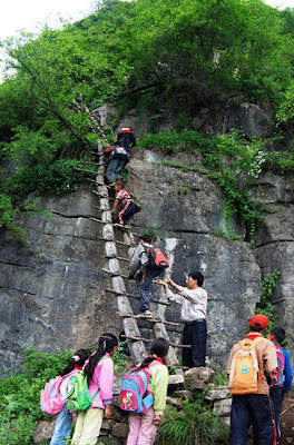 Teacher Li Guilin helps children climb one of five rickety wooden ladders to reach their school on a cliff 2,800m above sea level, in Gangluo County, Sichuan Province, China. The children would spend the week at the school before repeating  the dangerous journey in order to get home for the weekend...Picture: Quirky China News / Rex Features