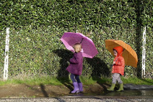 Fotografia di due bambini con ombrelli colorati