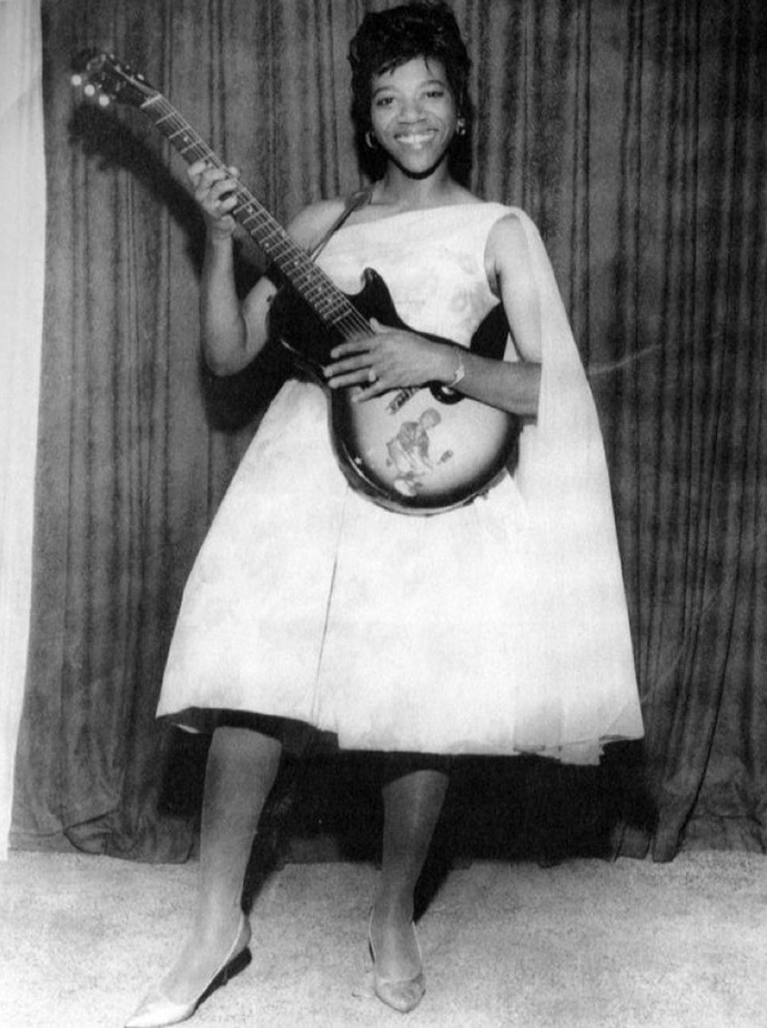 Barabara Lynn, with a white dress and guitar