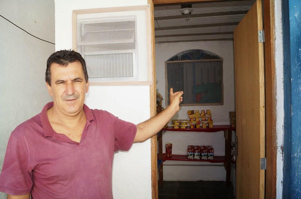 O pai de aluno Roberto Rodrigues mostra o depósito de alimentos que ajudou a construir na escola