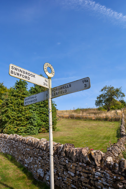 Cotswold stone wall and Cotswold signpost under a blue sky by Martyn Ferry Photography
