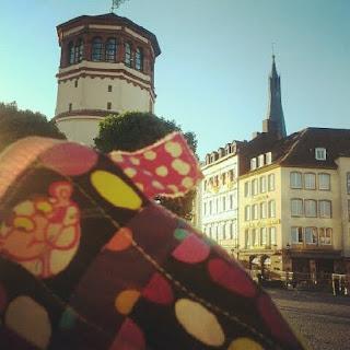 Tilkkupantteri-vetoketjupussukka maailman nähtävyyksien äärellä. Düsseldorf.