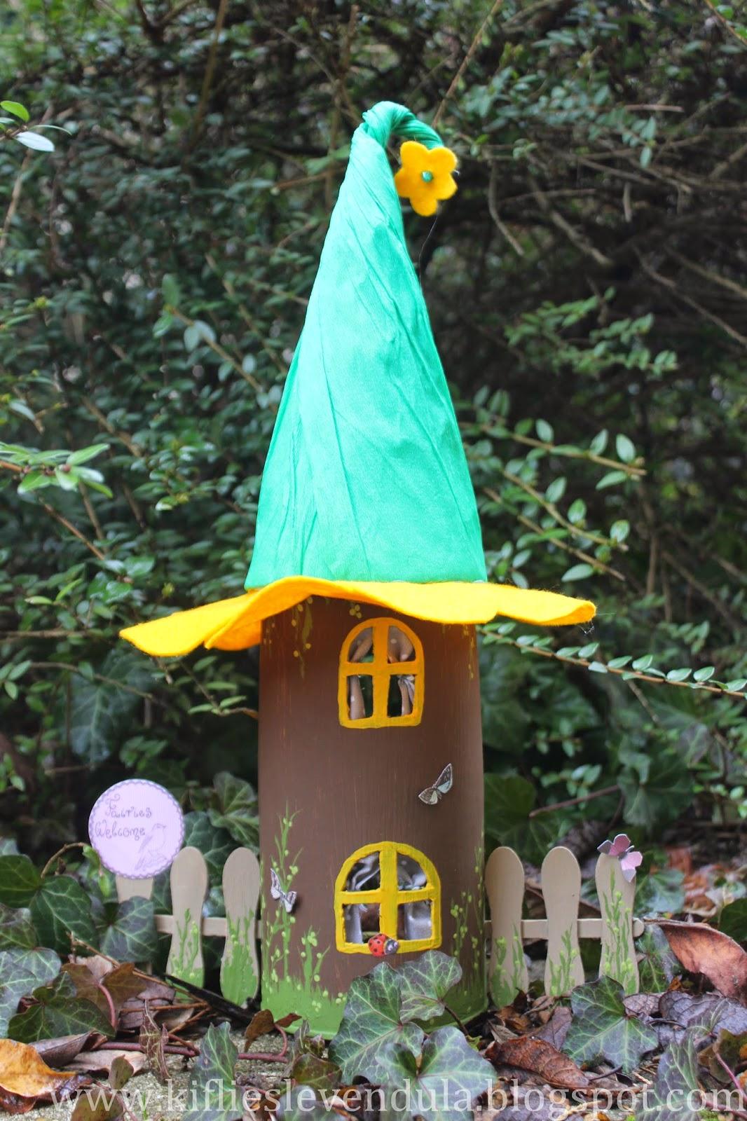 Casita de duendes hecha con un tubo de cartón y decorada.