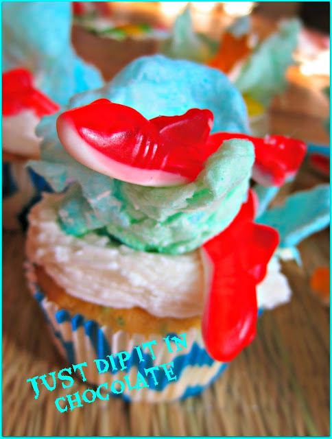 "Shark Week ""Sharknado"" Cupcakes Recipe, Shark Week will never be the same after you take a bite our of these fun cupcakes, Filled with a ""Bloody"" delicious raspberry filling they are great for a creepy Luau, a Halloween Hawaiian Gathering or just plain fun!"