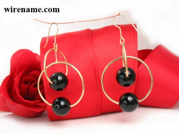 Dangling earings, two perpendicular circles in gold wire with black onyx beads